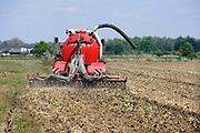 Nederland, Ooij, 4-5-2020 Een loonwerker rijdt met een tractor over het land om mest in de grond, bodem te injecteren. De injecteermachine wordt steeds gevuld vanuit een gesloten laadbak waar vrachtwagens gier in pompen. Vervolgens wordt het dus naar de tractor en op het land uitgereden . Open gieren mag niet meer, is verboden, vanwege de hoge ammoniak uitstoot.Foto: Flip Franssen