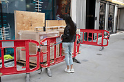 Young woman desperate for the best angle props her smart phone onto some building materials to take a selfie on New Bond Street in Mayfair, London, England, United Kingdom. Bond Street is one of the principal streets in the West End shopping district and is very upmarket. It has been a fashionable shopping street since the 18th century. The rich and wealthy shop here mostly for high end fashion and jewellery.