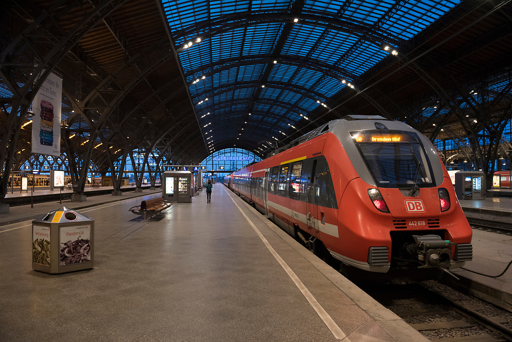 Leipzig, Germany - September 6, 2015: At dusk, a Dresden-bound train sits in the train station in Leipzig, Germany. A passenger walks on the platform while using her smart phone.