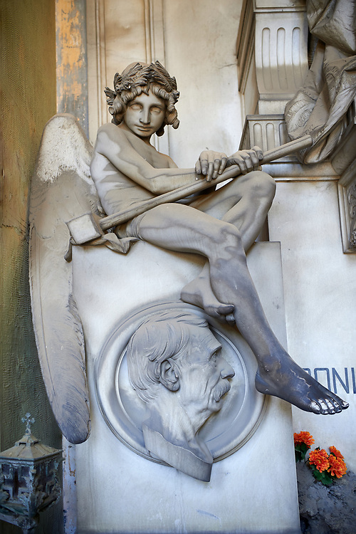 Picture and image of a stone sculpture of an angel by Sculptor V. Lavezzari 1897 on the Repetto tomb. The angel is holding a club and has a vacant look in its eyes giving it a mysterious sense of death. Section A, no 52, The monumental tombs of the Staglieno Monumental Cemetery, Genoa, Italy .<br /> <br /> Visit our ITALY PHOTO COLLECTION for more   photos of Italy to download or buy as prints https://funkystock.photoshelter.com/gallery-collection/2b-Pictures-Images-of-Italy-Photos-of-Italian-Historic-Landmark-Sites/C0000qxA2zGFjd_k<br /> If you prefer to buy from our ALAMY PHOTO LIBRARY  Collection visit : https://www.alamy.com/portfolio/paul-williams-funkystock/camposanto-di-staglieno-cemetery-genoa.html