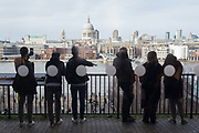Spectators look out over the Thames to St. Pauls Cathedral from the balcony on the third floor of Tate Modern, on 10th March 2019, in London, England.