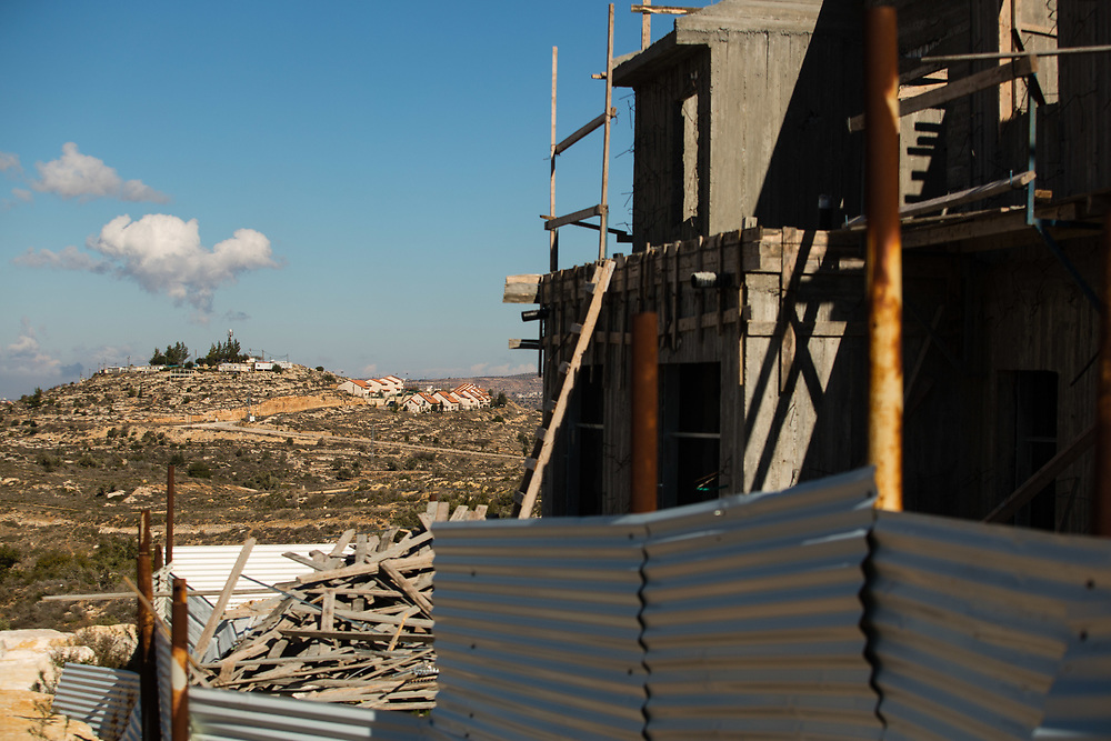 Built houses are seen in the background behind a construction site at the West Bank Jewish settlement of Eli, located south of the Palestinian West Bank town of Nablus, on January 1, 2017.