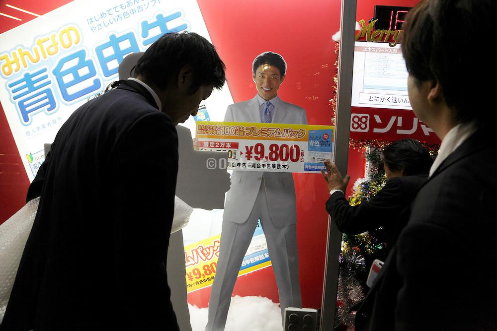 businessmen sales clerks working on a sales window display at Big Camera Tokyo Ginza Yurakucho