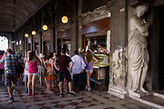Tourists queue for expensive gelato and cold drinks inside the covered Procuratie Nuovo in Piazza San Marco, Venice, Italy.