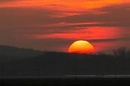 The sun sets behind Black Dirt fields in Pine Island, N.Y., on Dec. 10, 2020.