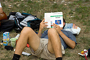 student studying biochemistry outdoors laying on the grass