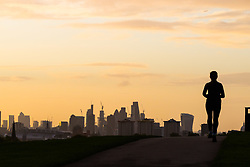 London, September 11 2017. A runner reaches the summit of Primrose Hill creating a silhouette against the London skyline as a new day breaks over the city. © Paul Davey