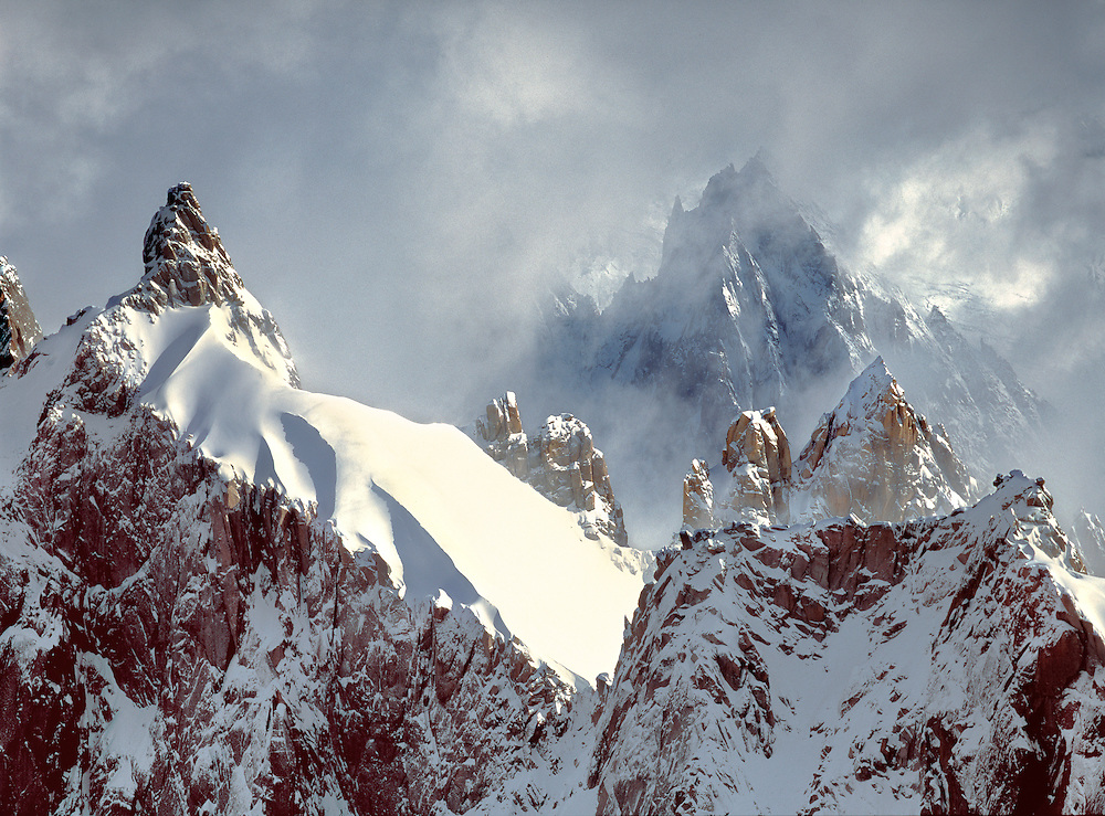 Jagged spires reach for the clouds at Aiguilles du Midi above Chamonix, France.
