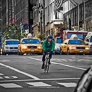A cyclist amid the taxi cabs