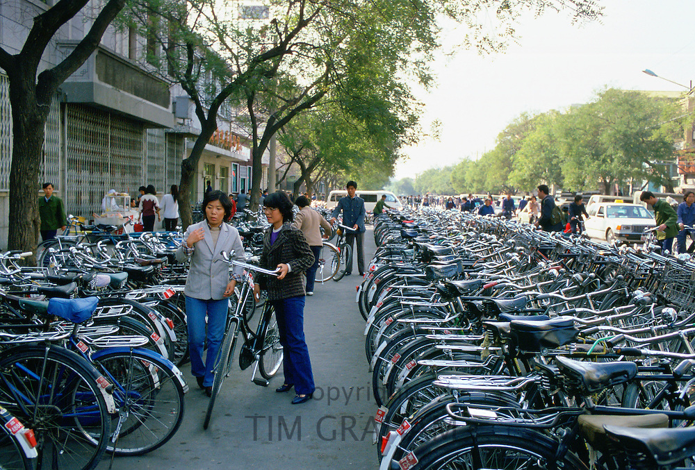 Young women parking bicycle in crowded bicycle park, Beijing, China