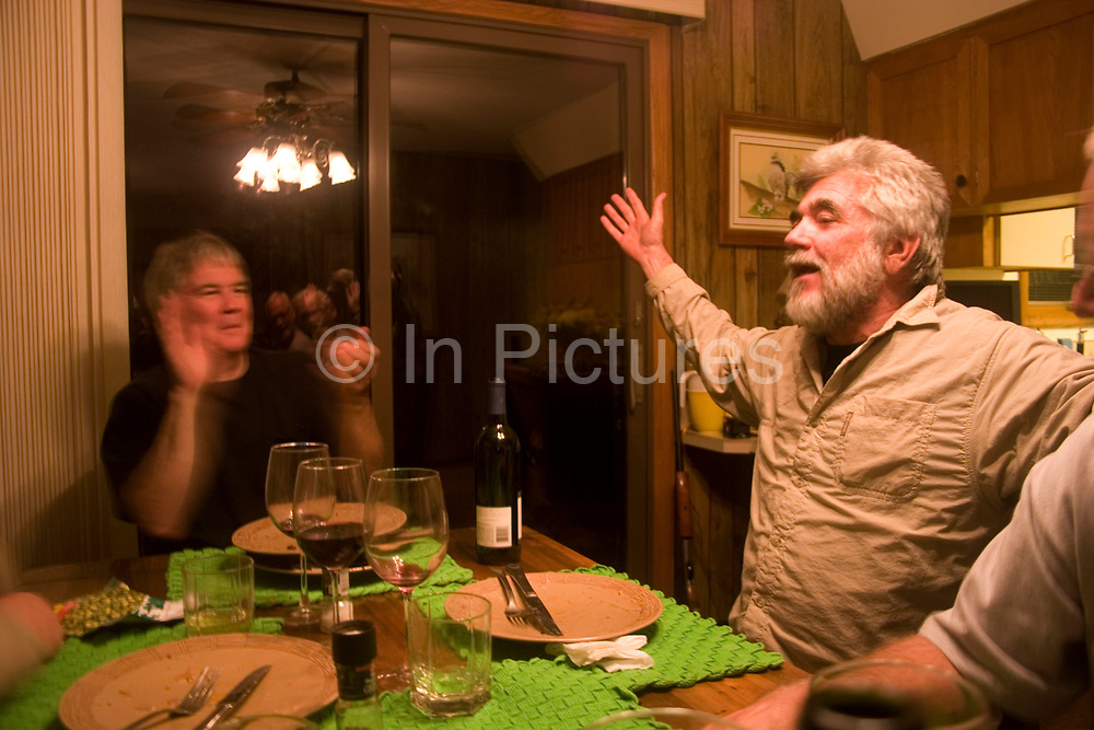 Hunter Byron Grubb's home in Burlington near Minot, North Dakota is full of the guns, trophies, stuffed animals and hunting paraphernalia of an experienced hunter. Here, his friend and fellow hunter John Davidson tells an amusing army story after the hunters evening meal.