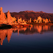 Unique tufa formations (calcium carbonate) in Mono Lake with the eastern escarpment of the Sierra Nevada Mountains behind. Mono Lake, CA.