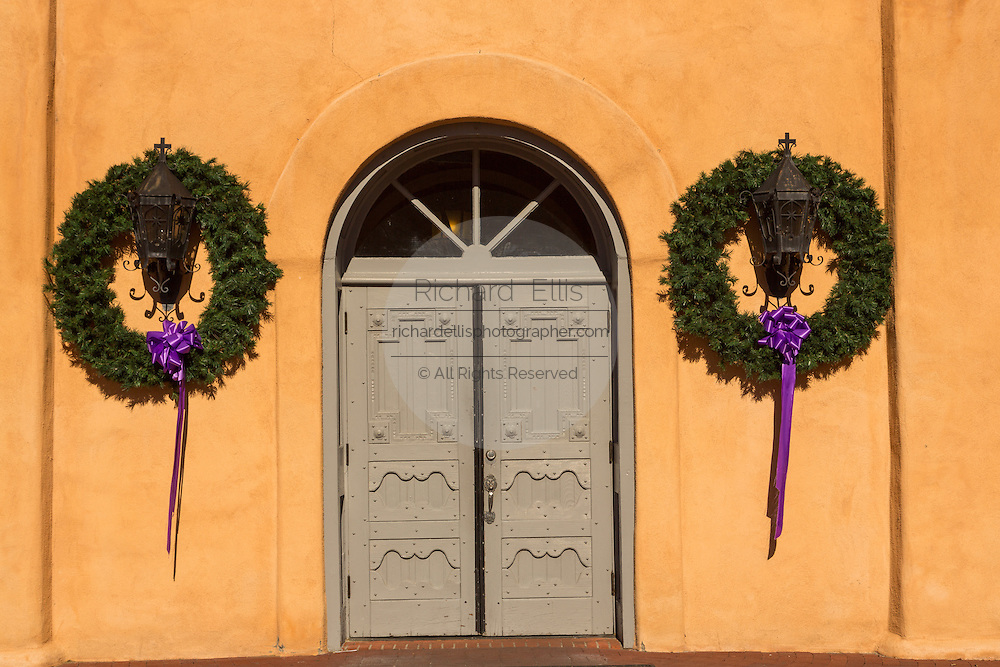Christmas wreaths along the doorway to San Felipe de Neri Church, historic adobe style Catholic church in the Old Town Plaza December 14, 2015 in Albuquerque, New Mexico.