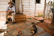 Man sitting on steps smoking cigarette outside a farmhouse near Vinales, Cuba.