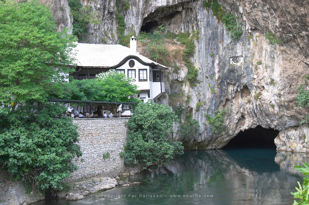 The source of the Buna river at the old Muslim monastery called the House of the Whirling Dervishes, below an impressive vertical cliff drop. The source of the Buna river and the house of the Whirling Dervishes, an old Muslim monastery, Blagaj. Federation Bosne i Hercegovine. Bosnia Herzegovina, Europe.