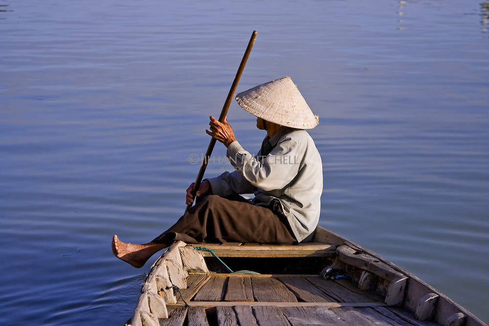 Old boat man sitting at the front of his small boat on the Thu Bon river in Hoi An.