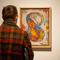 London, UK - 13 February 2013: a visitor looks up at Jasper Johns's 'Figure 8, 1959' at the 'The Bride and the Bachelors - Duchamp with Cage, Cunningham, Rauschenberg and Johns' exhibition that opens to the public on 14 February and runs until 9 June 2013 at Barbican. It is the first exhibition to explore Marcel Duchamp's impact on four great modern artists - composer John Cage, choreographer Merce Cunningham and visual artists Robert Rauschenberg and Jasper Johns.