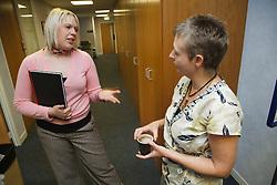 Women in office corridor.