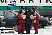 Moscow, Russia, 02/01/2004..Customers at the Martkauf shopping mall wait for private bus service for shoppers. A family reading holiday brochures while waiting.