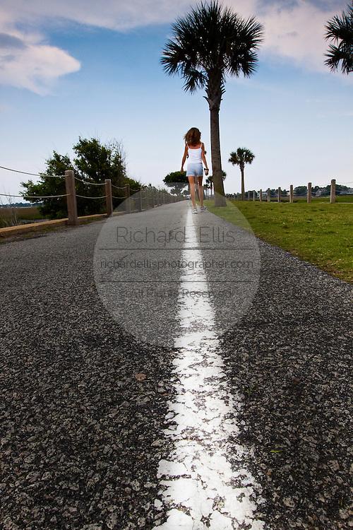 Women walking along a white line. (photo by Charleston SC photographer Richard Ellis)