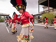 """03 DECEMBER 2011 - PHOENIX, AZ:   Matachine dance troupes perform during a procession to honor the Virgin of Guadalupe in Phoenix Saturday. The Phoenix diocese of the Roman Catholic Church held its Sixth Annual Honor Your Mother Day Saturday to honor the Virgin of Guadalupe. According to Mexican Catholic tradition, on December 9, 1531 Juan Diego, an indigenous peasant, had a vision of a young woman while he was on a hill in the Tepeyac desert, near Mexico City. The woman told him to build a church exactly on the spot where they were standing. He told the local bishop, who asked for some proof. He went back and had the vision again. He told the lady that the bishop wanted proof, and she said """"Bring the roses behind you."""" Turning to look, he found a rose bush growing behind him. He cut the roses, placed them in his poncho and returned to the bishop, saying he had brought proof. When he opened his poncho, instead of roses, there was an image of the young lady in the vision. The Virgin is now honored on Dec 12 in Catholic churches throughout Latin America and in Hispanic communitied in the US.    PHOTO BY JACK KURTZ"""