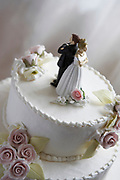 Angry man and woman statuettes on the top of a wedding cake with their backs to one another