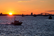 A United States Coast Guard USCG boat sails across the Upper Bay, New York City, New York, United States of America,  at sun set other boats also travel across the water and the Bayonne Bridge and building of New Jersey are silhouetted in the background.