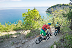 Mountain bikers moving downhill with sea in background
