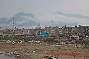 Typical landscape scene in Kathmandu, Nepal.  In the foreground is waste land bordering  onto some slum settlements. Behind are apartment blocks and infrastructure of the city.  In the background the Himalayan mountain range is surrounded by white clouds.