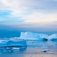 Sunset near the Lemaire Channel paints a landscape of icebergs into pastel.