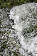 Bubbling water rushes by moss at the the mill race at Skinner's Mill, Painswick