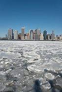 New York, the port of New York . the East river frozen and covered with ice, in the distance the cityscape of lower Manhattan, view from Brooklyn piers.