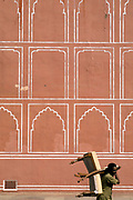 A man carries two chairs past the painted walls of the City Palace, Jaipur, India<br /> The City Palace is a complex of palaces in central Jaipur built between 1729 and 1731 by Jai Singh II, the ruler of Amber