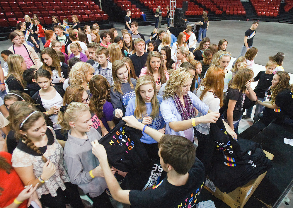 Participants gather to receive T-shirts during a music performance workshop hosted by The Young Americans Tuesday at the Heartland Events Center. The Young Americans is a group of trained performers ages 18-24 that travel around the world to dance and sing with students and provide learning opportunities.This years cast of cast of 46 members included five former Northwest High School Students. (Independent/Matt Dixon)