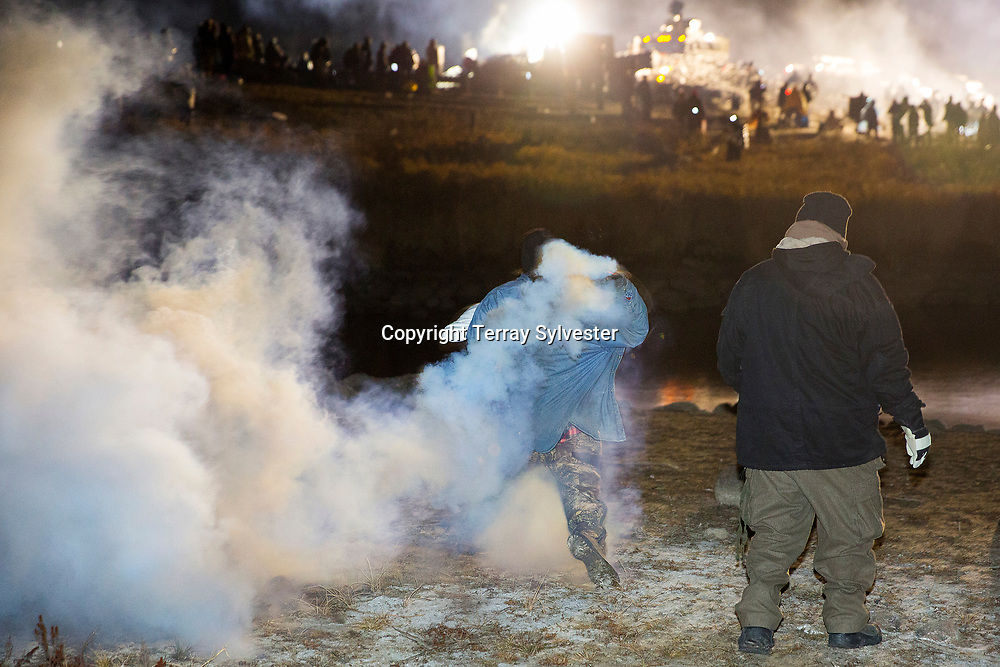 An opponent of the Dakota Access oil pipeline hurls a teargas canister back at police during a standoff on Backwater Bridge near the pipeline route on November 20, 2016. Cannon Ball, North Dakota, United States.