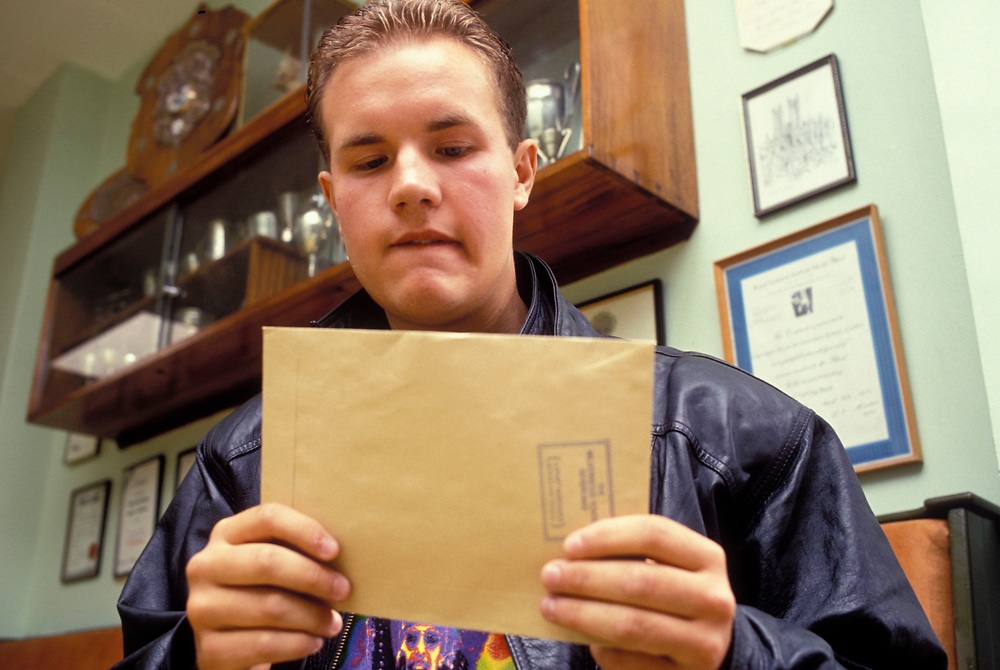 Sixth form student with his unopened A Level results in envelope; UK