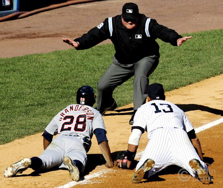 The Yankees' Alex Rodriguez (R) and Detroit Tigers' Curtis Granderson look up to the umpire after a close play at third during the American League Division Series on Thursday 05 October 2006.