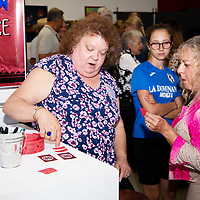 Tera Selleck, left, gives people their tickets and explains how to cast their vote for the People's Choice Award at the Best of Show Night at ART123 Gallery Tuesday evening.