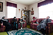 """Khalil sits with Misty, Abdul-Hakim and their friend Ruth, one of the only other Muslims living in Parsons, after Friday morning prayers in the Holmes' living room on March 8, 2013. """"Right now, being Muslim in Parsons, Kansas is really going against the grain,"""" Abdul-Hakim said."""