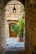 "Passageway in Saint Paul de Vence in France.<br /> -----<br /> Saint-Paul or Saint-Paul-de-Vence is a commune in the Alpes-Maritimes department in southeastern France. One of the oldest medieval towns on the French Riviera, it is well known for its modern and contemporary art museums and galleries such as Fondation Maeght which is located nearby. It was probably between the 10th and 12th century that a settlement formed around the ancient church of Saint Michel du Puy to the south, and near the castle on the highest part of the hill. In the Middle Ages, the region was administered by the Counts of Provence. In the 13th century, Count Charles II granted more privileges to St. Paul, including the right to hold a weekly market. At the beginning of 14th century, St. Paul acquired more autonomy and became a prosperous city of merchants and nobility. In 1388, the County of Nice broke off from Provence to reattach itself with the states belonging to the Count of Savoy. These new circumstances gave St. Paul a strategic position: the city becomes a border stronghold for five centuries. St. Paul went through its first fortification campaign in the second half of 14th century: the north gate of the city, called ""Porte de Vence,"" dates back to the medieval wall. At the time of the wars of Italy, Provence was invaded twice by the troops of Charles V. Considering the low side of the border of Provence and the obsolescence of the medieval fortifications in Saint-Paul, Fran�ois 1st decided in 1538 to build the new city walls, able to withstand the power of the artillery. This fortified wall, built between 1543 and 1547, is preserved in its entirety. On its northern and southern fronts four solid bastions protect both the city gates. In the 17th century, Saint-Paul experienced a religious period through the influence of Antoine Godeau, Bishop of Vence. The church was elevated to college, and was expanded and embellished. St. Paul also saw an urban revival thanks to the families of nobility, w"