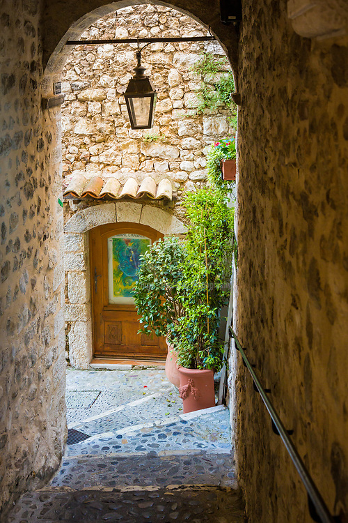 """Passageway in Saint Paul de Vence in France.<br /> -----<br /> Saint-Paul or Saint-Paul-de-Vence is a commune in the Alpes-Maritimes department in southeastern France. One of the oldest medieval towns on the French Riviera, it is well known for its modern and contemporary art museums and galleries such as Fondation Maeght which is located nearby. It was probably between the 10th and 12th century that a settlement formed around the ancient church of Saint Michel du Puy to the south, and near the castle on the highest part of the hill. In the Middle Ages, the region was administered by the Counts of Provence. In the 13th century, Count Charles II granted more privileges to St. Paul, including the right to hold a weekly market. At the beginning of 14th century, St. Paul acquired more autonomy and became a prosperous city of merchants and nobility. In 1388, the County of Nice broke off from Provence to reattach itself with the states belonging to the Count of Savoy. These new circumstances gave St. Paul a strategic position: the city becomes a border stronghold for five centuries. St. Paul went through its first fortification campaign in the second half of 14th century: the north gate of the city, called """"Porte de Vence,"""" dates back to the medieval wall. At the time of the wars of Italy, Provence was invaded twice by the troops of Charles V. Considering the low side of the border of Provence and the obsolescence of the medieval fortifications in Saint-Paul, Fran�ois 1st decided in 1538 to build the new city walls, able to withstand the power of the artillery. This fortified wall, built between 1543 and 1547, is preserved in its entirety. On its northern and southern fronts four solid bastions protect both the city gates. In the 17th century, Saint-Paul experienced a religious period through the influence of Antoine Godeau, Bishop of Vence. The church was elevated to college, and was expanded and embellished. St. Paul also saw an urban revival thanks to the families of n"""