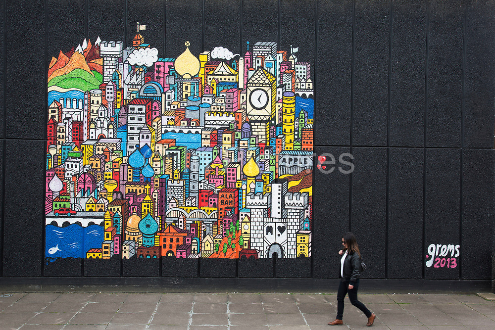 Woman walks past a piece of street art by artist Grems. The South Bank is a significant arts and entertainment district, and home to an endless list of activities for Londoners, visitors and tourists alike.