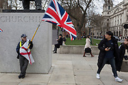 On the day that Prime Minister Theresa May's Meaningful Brexit vote is taken in the UK Parliament, a Leave supporter comes face to face with a tourist beneath the statue of Winston Churchill in Parliament Square, on 15th January 2019, in Westminster, London, England.