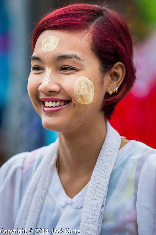 16 SEPTEMBER 2014 - SANGKHLA BURI, KANCHANABURI, THAILAND: A Mon Burmese woman with thanaka powder on her face waits to present Mon Buddhist monks with food and other offerings during the morning alms rounds in the Mon community in Sangkhla Buri.  The Mon were some of the first people to settle in Southeast Asia, and were responsible for the spread of Theravada Buddhism in Thailand and  Indochina. The Mon homeland is in southwestern Thailand and southeastern Myanmar (Burma). The Mon in Thailand traditionally allied themselves with the Thais during the frequent wars between Burmese and Siamese Empires in the 16th - 19th centuries and the Mon in Thailand have been assimilated into Thai culture. The Mon in Myanmar were persecuted by the Burmese government and many fled to Thailand. Sangkhla Buri is the center of Burmese Mon culture in Thailand because thousands of Mon came to this part of Thailand during the persecution.    PHOTO BY JACK KURTZ