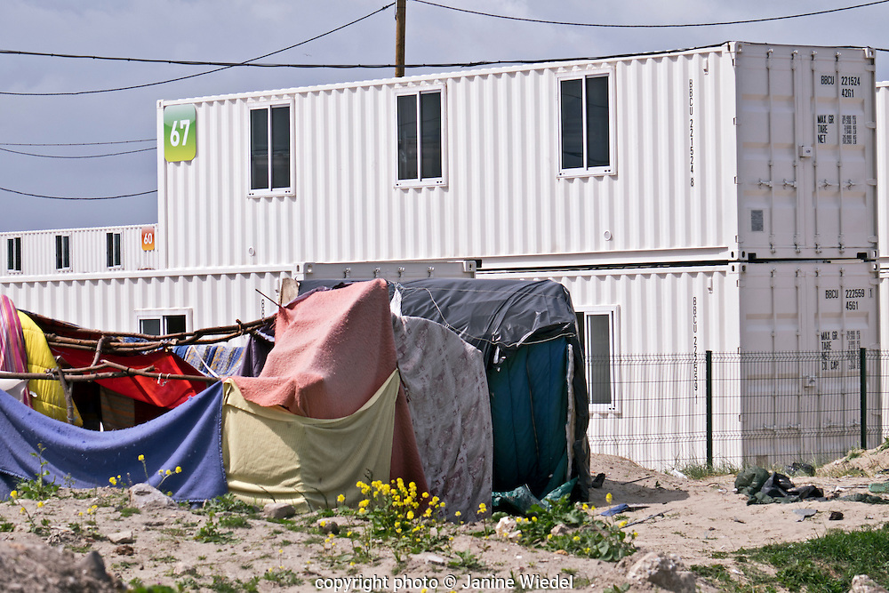 Contrasting of makeshift dwellings and new shiping containers converted to accommodating refugees and migrants at The Calais Jungle Camp in France