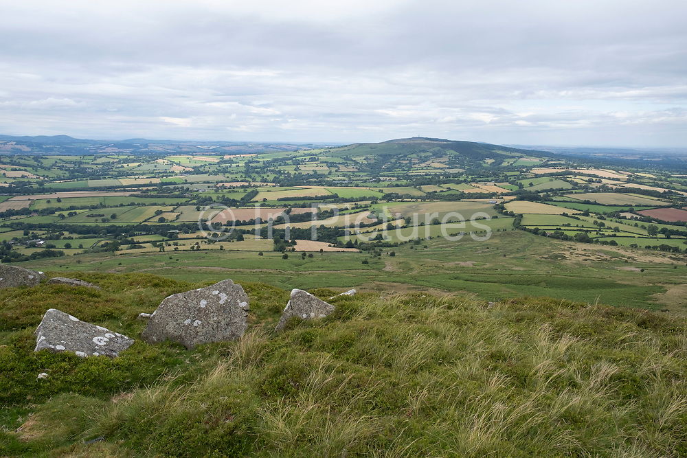 View from Titterstone Clee Hill looking towards Brown Clee Hill on 22nd July 2020 in Cleedownton, United Kingdom. Titterstone Clee Hill, sometimes referred to as Titterstone Clee or, incorrectly, Clee Hill, is a prominent hill in the rural English county of Shropshire, rising at the summit to 533 metres above sea level. It is one of the Clee Hills, in the Shropshire Hills Area of Outstanding Natural Beauty. Most of the summit of the hill is affected by man-made activity, the result of hill fort construction during the Bronze and Iron Ages and, more recently, by years of mining for coal and quarrying for dolerite, known locally as dhustone, for use in road-building. Many derelict quarry buildings scattered over the hill are of industrial archaeological interest as very early examples of the use of reinforced concrete. Several radar domes and towers operate on the summit of the hill. The largest of the radar arrays is part of the National Air Traffic Services NATS radar network, and covers one of 30 overlapping regions of UK airspace. The one on Titterstone Clee monitors all aircraft within a 100-mile radius.