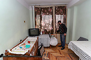 """Koropetyan Armen stands in his living room hotel suite of previously abandoned building of """"SOVIET Hotel"""" in Metsamor. Kropetyan is 45 years old and father of six children. He says they will not return to Nagorno Karabakh. (Photo/ Vudi Xhymshiti)"""