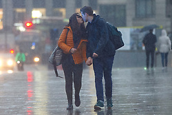 © Licensed to London News Pictures. 07/01/2016. London, UK. A couple kissing during a heavy rain on London Bridge in London on Thursday, 7 January 2016. Photo credit: Tolga Akmen/LNP