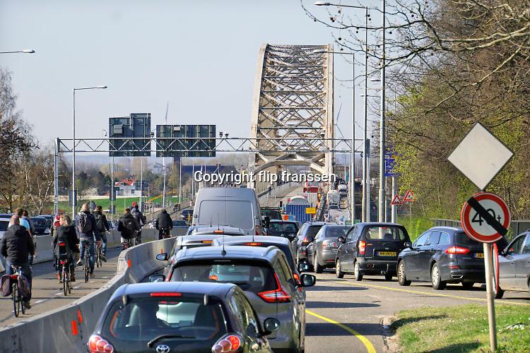 Nederland, Nijmegen, 2-4-2019 Aannemer KWS doet groot onderhoud aan de oude, iconische Waalbrug . De brug wordt de komene maanden grondig gerenoveerd en opgeknapt. Het bleek dat de oude verf chroom6 bevat waardoor de renovatie is uitgesteld vanwege extra veiligheidsmaatregelen. De brug is gebouwd in 1936 en was toen de langste boorbrug van Europa . Eerst wordt de onderkant onder handen genomen, en later wordt de brug opnieuw geschilderd als ook duidelijk is hoe de oude verf het beste verwijdert kan worden . Het verkeer kan mondjesmaat over de brug en dat veroorzaakt veel file en oponthoud op de A325 en N325Foto: Flip Franssen