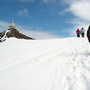 Visitors walking up a steep hill in the snow to reach Trinity Church, a Russian Orthodox church on King George Island in the South Shetland Islands. It is situated on a small rocky hill near Russian Bellingshausen Station research base. Constructed of Siberian cedar and pine with special reinforcements against the harsh weather of Antarctica, Trinity Church was consecrated in 2004 and is the southernmost Eastern Orthodox church in the world.